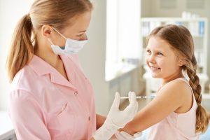 Criança sendo vacinada por uma mulher
