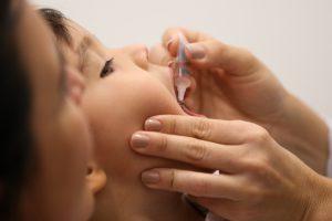 Criança tomando vacina contra poliomielite