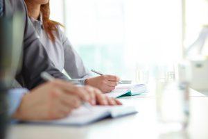 Dois pares de mãos escrevendo em cadernos
