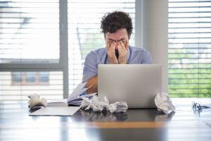 Homem em frente a um computador, com vários papeis amassados em volta e com as mãos nos olhos, angustiado