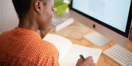 Mulher escrevendo em um caderno, em frente ao computador
