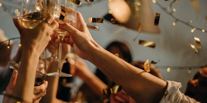 Pessoas brindando com uma taça de espumante em uma festa de fim de ano
