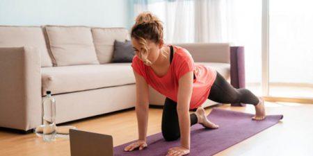 Mulher realizando exercício em casa, olhando para o notebook